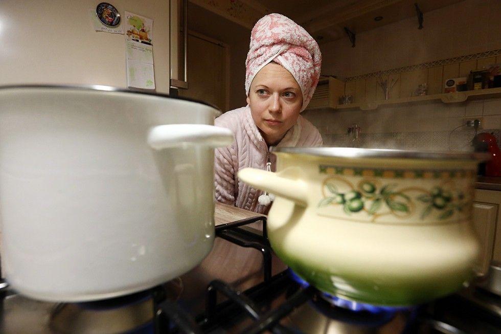 Russa prepara banho após desligamento de água quente (Foto: Aleksandr Rimin/TASS)
